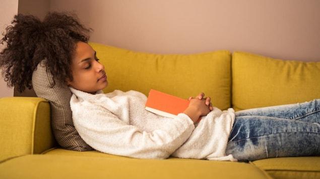 Une jeune femme endormie allongée sur un canapé, un livre ouvert posé sur elle.