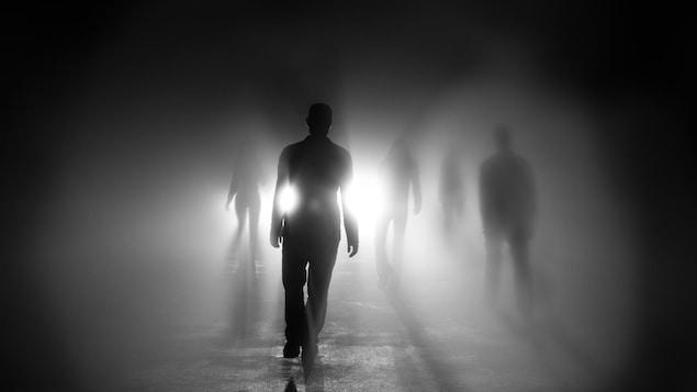 Des silhouettes visibles devant une lumière diffuse.