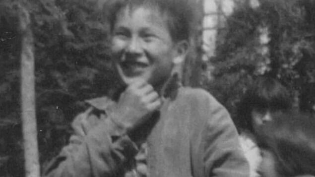 Un enfant sourit à la caméra