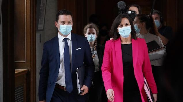 Simon Jolin-Barrette et Isabelle Charest marchant et portant tous deux un masque.