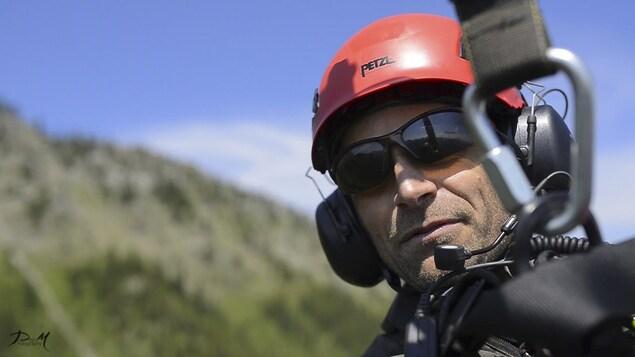 un homme en habit de secouriste, suspendu à un hélicoptère.
