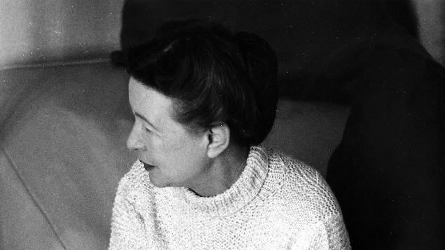 Simone de Beauvoir, assise sur un canapé.