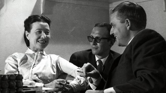 Simone de Beauvoir et Wilfrid Lemoine fumant une cigarette à une petite table. Claude Sylvestre est également assis avec eux, un peu en arrière-plan.