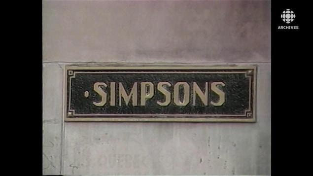 Plaque de métal avec le nom Simpsons encastrée sur l'édifice Simpson de la rue Sainte-Catherine, à Montréal.