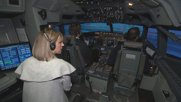 On voit l'intérieur de la cabine du simulateur de vol. Un pilote et un co-pilote sont assis aux commandes (on les voit de dos). Derrière eux, l'instructrice parle.
