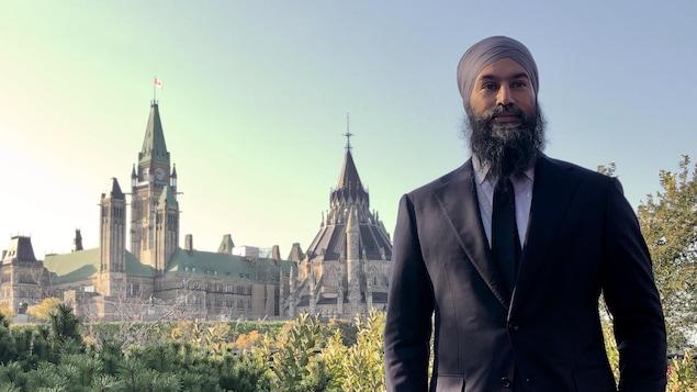 Jagmeet Singh debout avec le parlement d'Ottawa en arrière-plan.