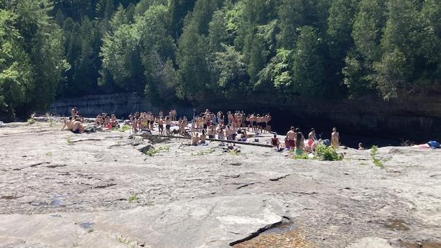 Plan large sur les abords d'une rivière où des groupes de personnes sont attroupés ici et là dans une ambiance festive et décontractée.