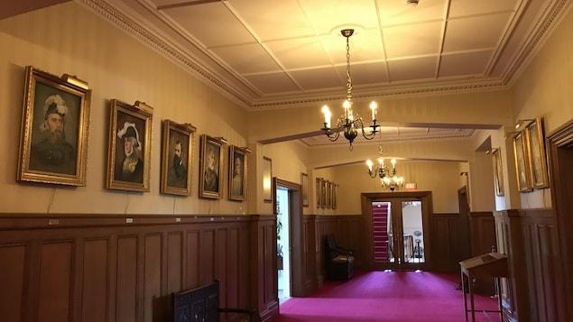 L'intérieur de la résidence du lieutenant-gouverneur de la Colombie-Britannique. Un corridor sur les murs duquel sont accrochés des portraits de gouverneurs.