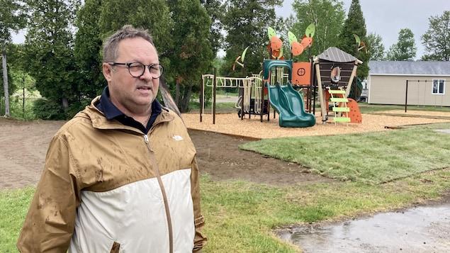 Un homme avec un imperméable parle dans un parc pour enfants.