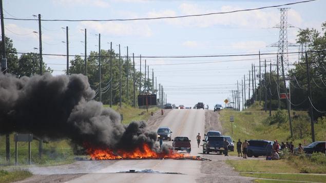 Des choses brûlent au milieu d'une route. Des gens regardent autour.