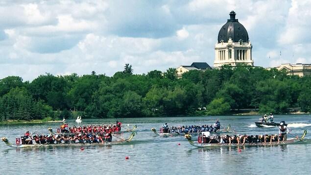Des bateaux avec de nombreux rameurs descendent une rivière devant un parc boisé.