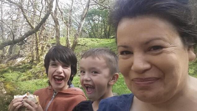 Une femme photographiée de près en compagnie de deux enfants.