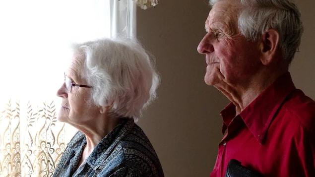 Un homme et une femme regardent par la fenêtre.