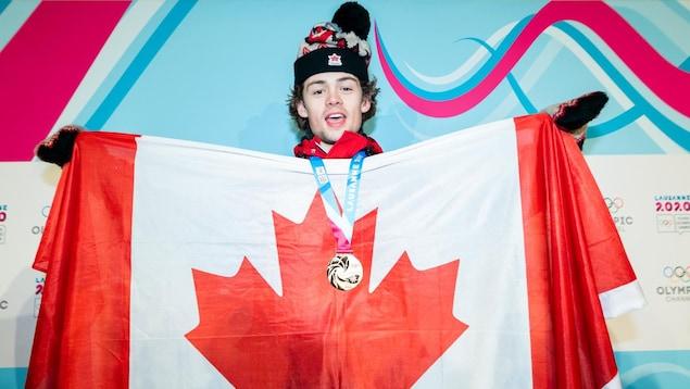 L'athlète porte sa médaille et tient un drapeau canadien devant son torse.