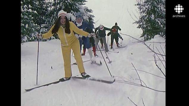 Groupe de skieurs qui monte une pente enneigée.