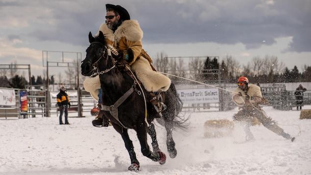 Un cavalier sur son cheval tire un skieur.