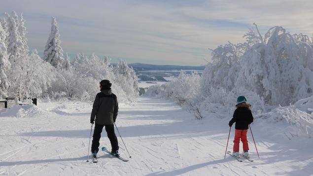 Un homme et une fillette descendent une pente du Mont-Comi lors d'une journée ensoleillée.