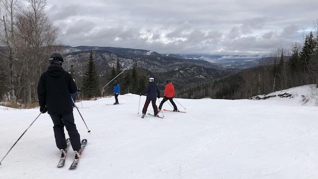 Des skieurs au sommet d'une montagne.