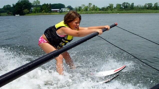 Sur une étendue d'eau, une fillette apprend à faire du ski nautique en se tenant à une barre de métal.