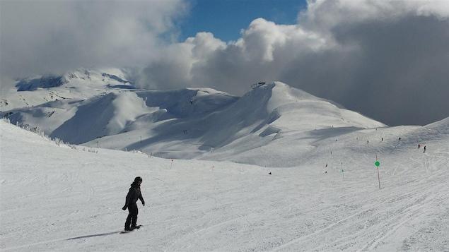 Un planchiste évolue le long d'une piste à Whistler en Colombie-Britannique
