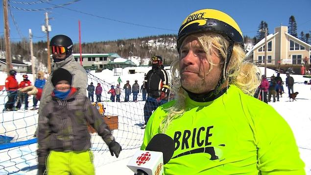 Un participant accorde une entrevue à Radio-Canada alors qu'il porte un costume inspiré du personnage de Brice de Nice.