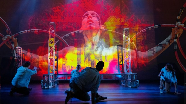 Trois interprètes accroupis regardant l'image, sur un écran, d'un danseur autochtone.