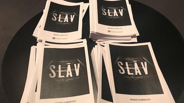 Quatre pile de feuillets en papier, avec la mention SLĀV.