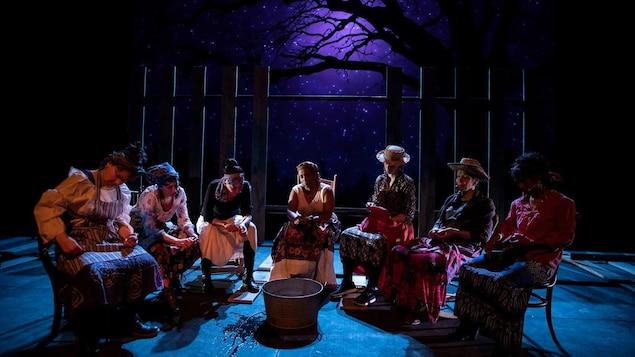 Septs femmes sont assises sur des chaises en train d'éplucher des pommes de terre dans une scène du spectacle <i`>SLĀV </i> présenté au Théâtre du Nouveau Monde à Montréal.