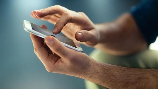 Un téléphone cellulaire entre les mains d'un homme.
