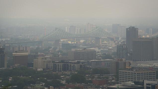 Une vue du pont Jacques-Cartier voilée par la fumée.