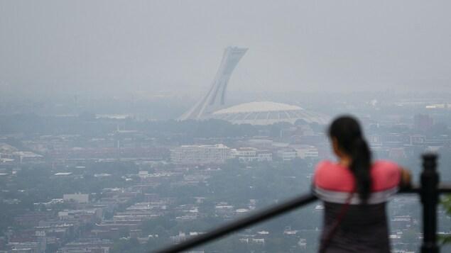 Une femme regarde le stade olympique de Montréal, appuyée contre une rambarde.