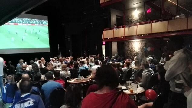Des gens regardent le match diffusé sur écran géant dans une salle de spectacle.
