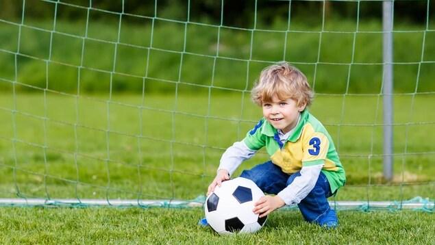 Un enfant tient un ballon de soccer devant un filet.