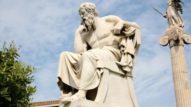 Vêtu d'une toge, Socrate est assis, pensif.