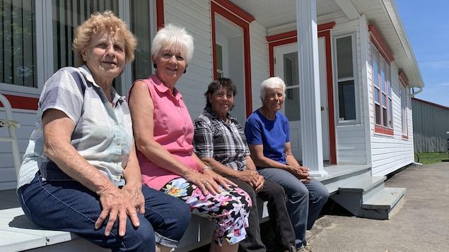 Quatre femmes assises sur le balcon d'une maison ancestrale l'été.
