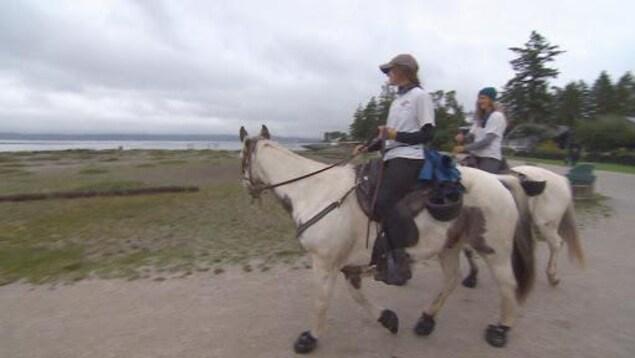 Les soeurs sont à cheval sur un sentier à Surrey à une centaine de mètres de la mer.