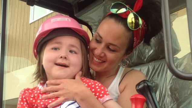 Mélanie Cossette tient dans ses bras sa fille Sofianne, lourdement handicapée