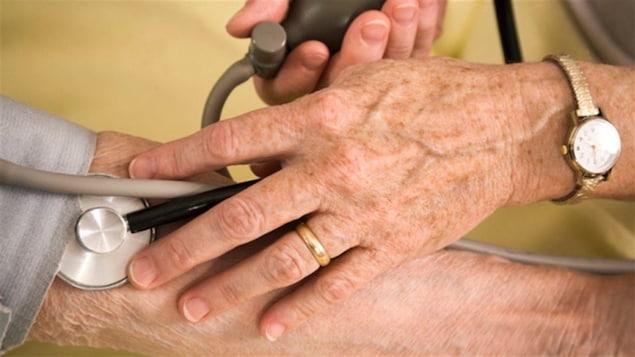 La main du médecin avec son appareil pour prendre la pression artérielle posé sur et le bras de la patiente.