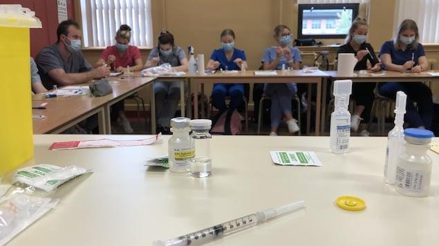 Une seringue et une fiole sur une table devant des étudiants assis à une autre table.