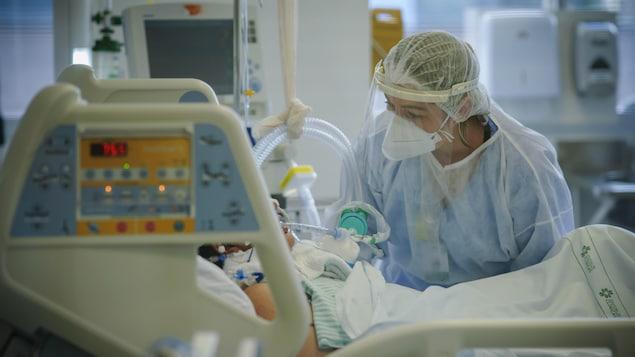 Une infirmière portant de l'équipement de protection se penche au-dessus du lit d'un patient.