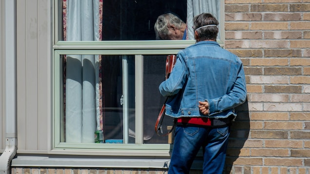 A loved one visits a resident of the Montfort Long Term Care Centre in Ottawa on April 20, 2020. (Jean Delisle/CBC)