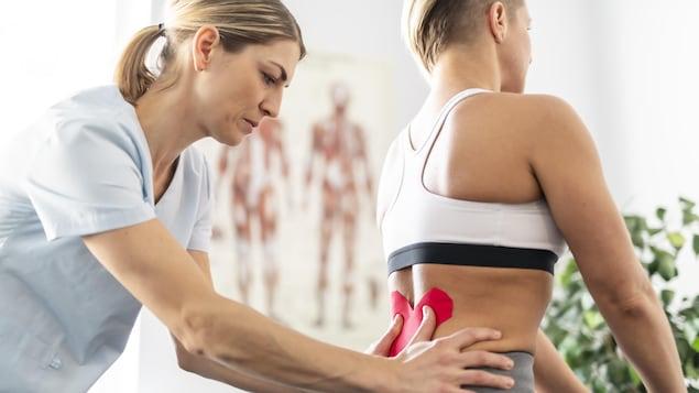 Une professionnelle de la santé applique un bandage sur le bas du dos d'une femme assise devant elle.