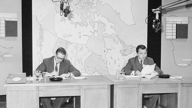 Pierre Stein et Wilfrid Lemoine, assis derrière des bureaux surmontés de cartes et tableaux.