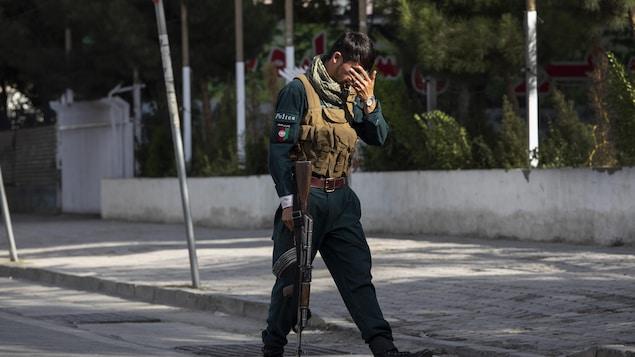Un soldat afghan se cache le visage dans les rues de Kaboul.