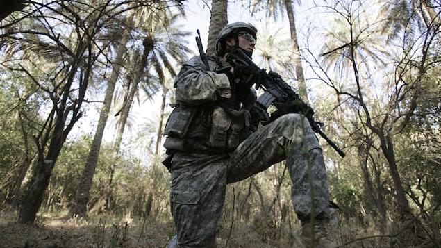 Soldat américain tenant une arme au milieu de palmiers