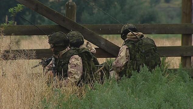 Une équipe de trois soldats de dans un champ près d'une clôture.