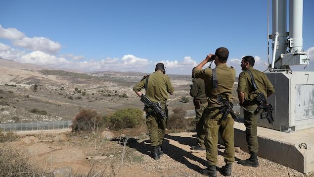 Quatre soldats israéliens regardent l'horizon depuis le plateau du Golan, qui surplombe le reste du territoire syrien.