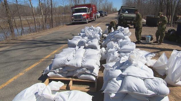Des soldats travaillent près de palettes de sacs de sable en bordure de route.