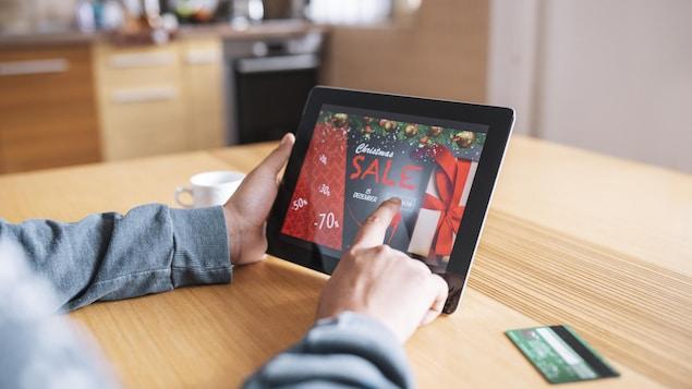 Une femme fait des achats en ligne à l'occasion des soldes de l'Après-Noël en utilisant une tablette numérique.