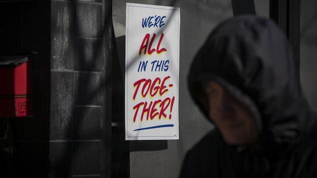 Une affiche de solidarité sur laquelle il est écrit en anglais « nous sommes tous ensemble dans cette situation » collée sur une vitrine d'un magasin torontois.